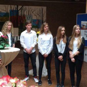 """Guido van den Berg MdL (rechts) überreicht die Ausstellung """"Der Weg zur Deutschen Einheit"""" an Schulleiter Dr. Hummelsheim (links) und Schülerinnen und Schüler des Erftgymnasiums."""