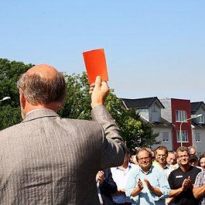 """Niederziers Bürgermeister Herrmann Heuser zeigt """"gewaltbereiten Aktivisten"""" symbolisch die rote Karte."""